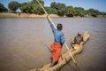 Men cross the Omo River near Turmi using a wooden boat, Ethiopia
