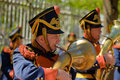 A men dressed in an old military uniform playing the trumpet with shako on his head sunny day Royalty Free Stock Image