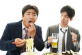 Men drinking beer drunk eating noodle and young looking at him Royalty Free Stock Photo