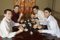 Men eating sushi with chopsticks in restaurant portrait of happy four the Stock Photo