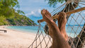 Men feet in Hammock, relaxing on the beach in Haad Rin, Ko Phangan Royalty Free Stock Photo