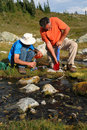 Men Filtering Water from Mountain Stream 4 Royalty Free Stock Photo