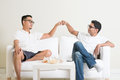 Men fist bump man sitting on sofa and giving to friend at home multiracial people friendship Royalty Free Stock Photo