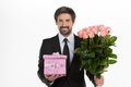 Men with gift box and flowers cheerful young man in formalwear holding a bunch of in his hands while standing against white Royalty Free Stock Photography