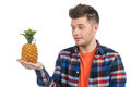 Men with grapes cheerful young man holding pineapple and looking at it while standing isolated on white Stock Photo
