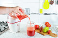 Men hands pouring fresh juce in to big jars to be served fresh vegetable juice kitchen interior Royalty Free Stock Images