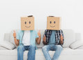 Men with happy smiley boxes over faces gesturing thumbs up while sitting on sofa Stock Photography
