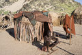 Man of the himba tribe in Namibia sitting in front of his hut Royalty Free Stock Photo