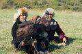 Men hold golden eagles Aquila chrysaetos, Almaty, Kazakhstan. Royalty Free Stock Photo