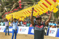 Men hold up sections of a Japanese kite on Negombo beach in Sri Lanka. Royalty Free Stock Photo