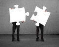 Men holding two puzzles Royalty Free Stock Photo