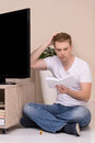 Men with instruction manual frustrated young man reading a tv Royalty Free Stock Photography