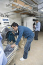 Men loading clothes in washing machine at laundry full length of young Stock Photography