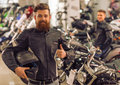 Men in motorbike salon handsome young bearded black leather jacket is holding a helmet showing ok sign and smiling while standing Royalty Free Stock Photos