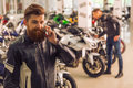 Men in motorbike salon handsome young bearded is talking on the mobile phone and smiling while standing a Royalty Free Stock Image