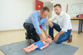 Men performing first aid on child sized dummy Royalty Free Stock Photo