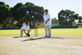Men playing cricket at pitch against clear sky Royalty Free Stock Photo