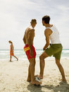 Men playing football look at a woman walking by the beach women Royalty Free Stock Photos