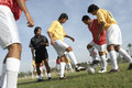 Men playing soccer while referee watching them low angle view of young on field Stock Image