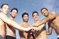 Men putting their hands on each others hands male friends having fun the beach Stock Image