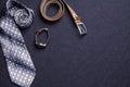 Men`s accessories on black background tie wallet watch strap sho
