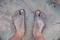 Men s barefoot feet in the sand Stock Images