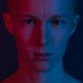 Men s beauty and fashion theme portrait of a handsome young guy with red and blue lighting on a dark background in the studio Royalty Free Stock Photos
