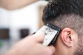 Men's hairstyling and haircutting with hair clipper in a barber Royalty Free Stock Photo