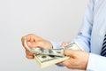 Men's hand holding money american hundred dollar bills. Hand of business man offering money. Royalty Free Stock Photo