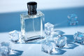 Men`s Perfume in transparent bottle with water droplets and pieces of ice around on blue background. Royalty Free Stock Photo