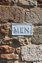 Men s toilet bathroom sign on brick wall a white washed painted metal or male a red portrait orientation Royalty Free Stock Images