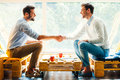 Men shaking hands side view of two happy young while sitting in front of the window Stock Image