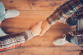 Men shaking hands top view of two while standing on the wooden floor Stock Image