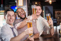 Men shout and rejoice in meeting and drink beer three other men drinking having fun together the bar Royalty Free Stock Photography