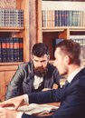 Men in suits, oldfashioned professors, scientists in library with books Royalty Free Stock Photo