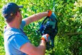 Men trimming hedge using powerful gasoline trimmer Royalty Free Stock Photo