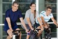 Men and woman on exercise bikes happy women in health club Royalty Free Stock Image