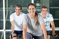 Men and woman on exercise bikes happy women in health club Stock Photos