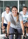 Men and woman on exercise bikes happy women in health club Royalty Free Stock Photo