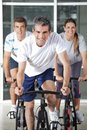 Men and woman on spinning bikes happy women in health club Stock Photography