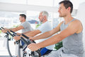 Men working out on exercise machines row of at fitness studio Stock Image