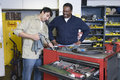 Men in workshop with tools two multiethnic Royalty Free Stock Images