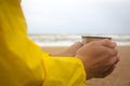Men in yellow raincoat on the beach over the stormy sea holding a cup of hot tea Royalty Free Stock Photo
