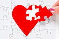 Mending a broken heart woman putting the missing piece of jigsaw red in place good image to represent love heartbreak romance or Royalty Free Stock Photo