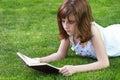 Menina bonita de park young que lê um livro exterior Imagem de Stock