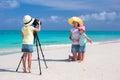 Menina bonito pequena que faz a foto de sua família na praia tropical Foto de Stock
