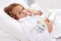 Menina com frio ruim - usando o pulverizador nasal Fotografia de Stock Royalty Free