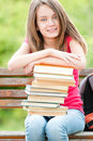 Menina feliz do estudante que senta-se no banco e no sorriso Imagens de Stock Royalty Free