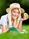 A menina no chapéu de palha com maçã lê o livro na grama verde Fotografia de Stock Royalty Free