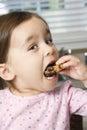 Menina que come o bolinho. Fotografia de Stock Royalty Free